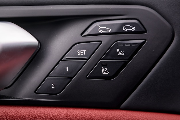 Painel de controle com alça cromada na porta do carro, couro genuíno preto comum em um carro novo. apoio de braço com ajuste de assento e painel de controle de tronco aberto