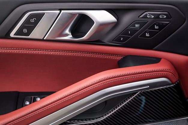 Painel de controle da porta com puxador cromado na porta do carro, couro genuíno preto e vermelho comum em um carro novo. apoio de braço com ajuste de assento e painel de controle de tronco aberto