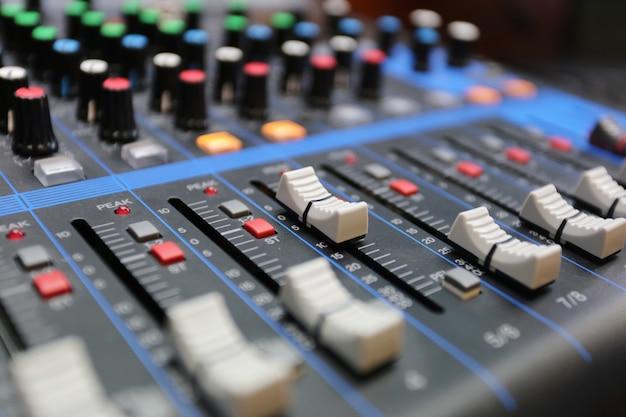 Painel de controle do mixer de áudio com botões e controles deslizantes.