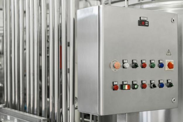 Painel de controle eletrônico e tanque em fábrica de leite. equipamento na fábrica de laticínios