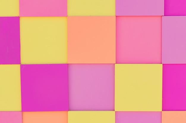 Painel de madeira multicolorido nas cores pastel rosa, amarelas e laranja