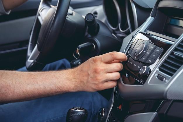 Painel do carro. close up do rádio. homem liga rádio
