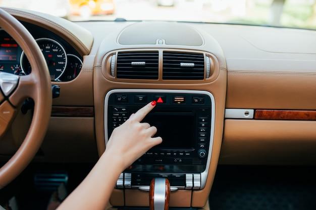 Painel do carro. close up do rádio. mulher liga o rádio