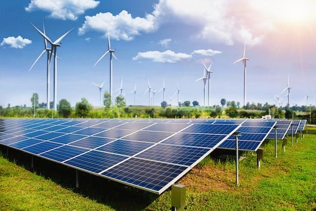 Painel solar com turbinas eólicas contra montanhas e céu