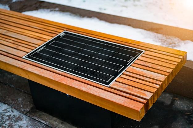 Painel solar construído no banco da cidade de madeira. banco inteligente
