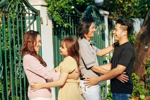 Pais abraçando filha e filho
