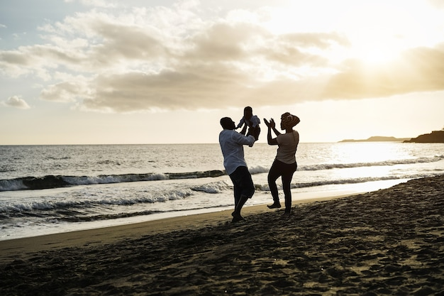 Pais africanos e filho se divertindo na praia ao pôr do sol - foco na silhueta