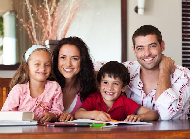 Pais agradáveis que ajudam seus filhos para a lição de casa