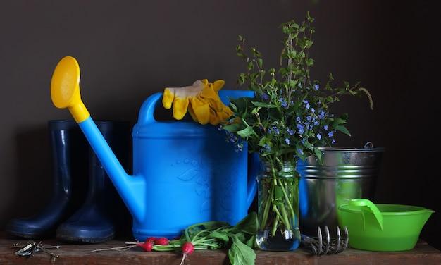 País ainda a vida. ferramentas de jardim em cima da mesa: rega, scratchy, balde, botas de borracha e luvas
