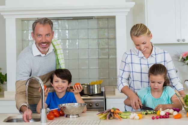 Pais ajudando crianças a cortar e limpar os legumes na cozinha