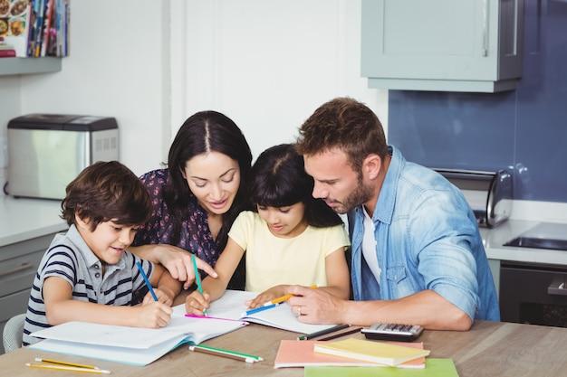 Pais ajudando crianças a fazer lição de casa