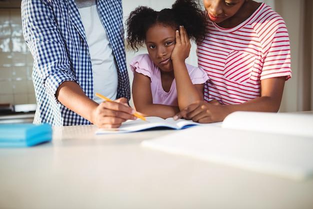 Pais ajudando filha com lição de casa