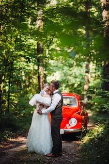Pais alegres andam com sua pequena filha antes do carro antiquado