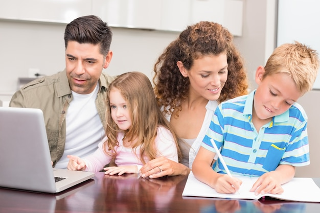 Pais alegres colorindo e usando o laptop com seus filhos