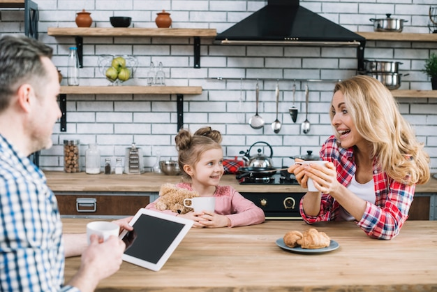 Pais alegres e filha desfrutando de pequeno-almoço na cozinha