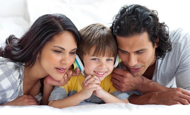 Pais alegres ouvindo música com seu filho