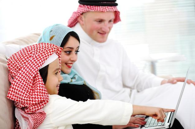 Pais árabes e garotinho em casa com laptop