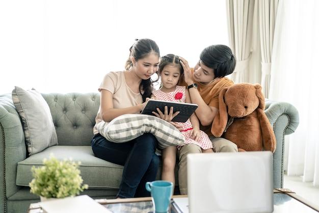 Pais asiáticos e uma criança olham para um laptop em casa. conceito de família.