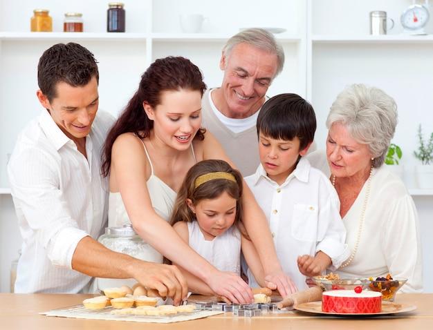 Pais, avós e filhos assando na cozinha
