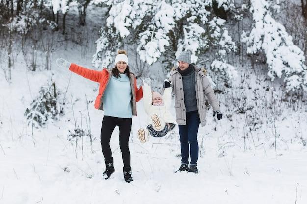 Pais balançando menina no inverno