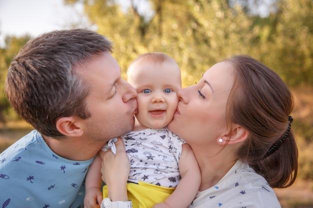 Pais beijam bebê em uma caminhada, sessão de fotos de família no verão