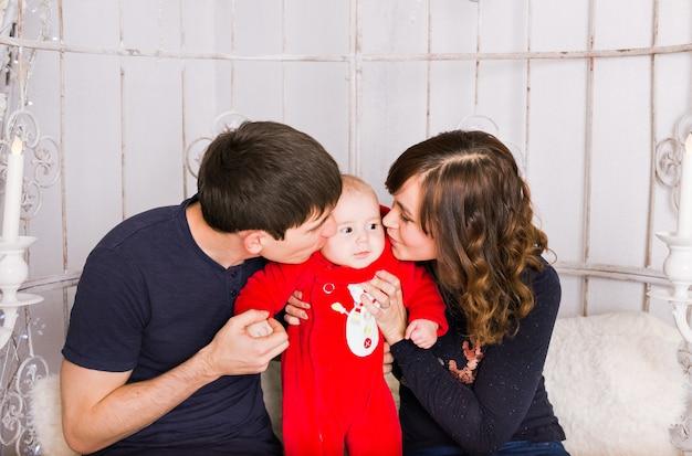 Pais beijando bebê recém-nascido. conceito de amor familiar