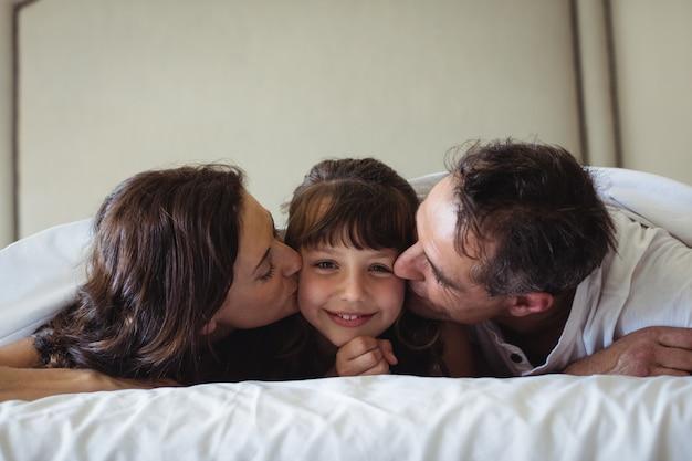 Pais beijando sua filha na bochecha no quarto