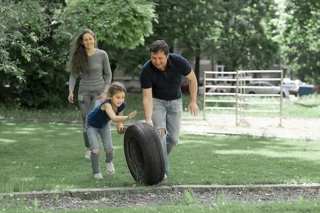Pais brincando com a filha no playground perto de casa. vida urbana