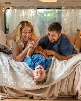 Pais brincando com o filho na cama