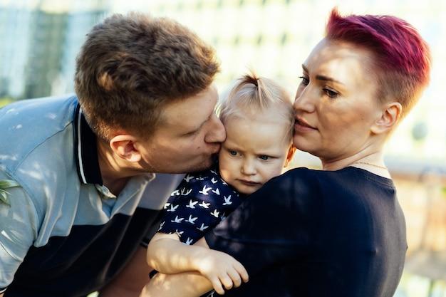 Pais caucasianos, homem e mulher, de uma menina beijando sua filha bebê