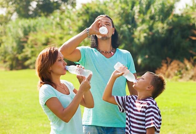 Pais com água bebendo adolescente