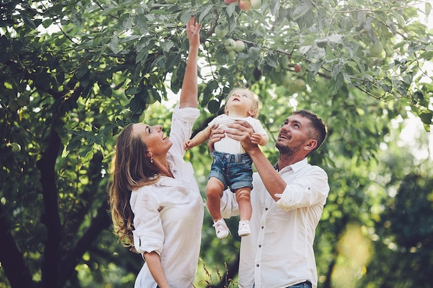 Pais com bebê fazendo piquenique em uma fazenda com macieiras e cerejeiras.