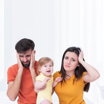 Pais com bebê sorridente com dor de cabeça