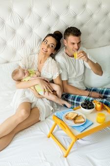 Pais com bebê tomando café da manhã na cama
