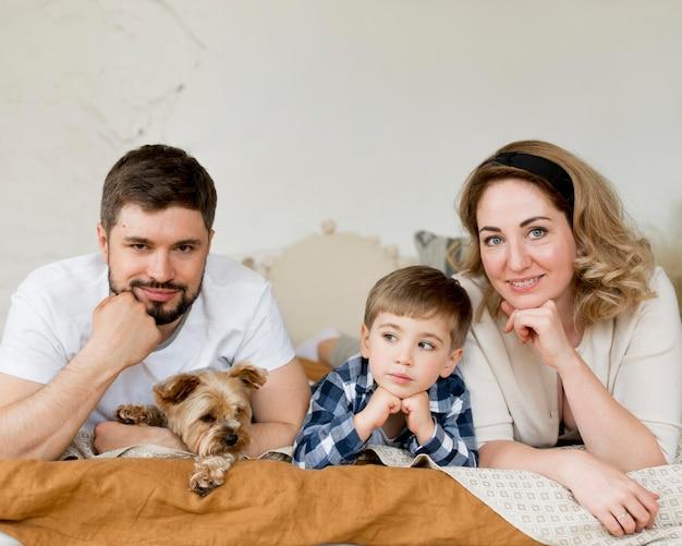 Pais com criança e cachorro sentado na cama