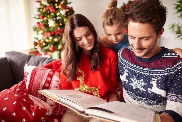 Pais com criança lendo livro no natal