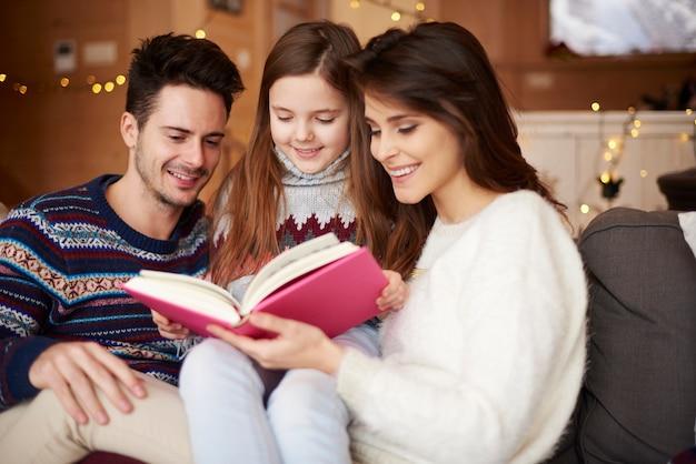 Pais com filha lendo contos de fadas
