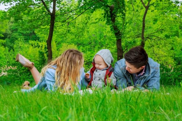Pais com filho brincando no gramado do parque