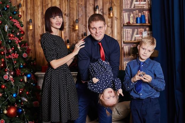 Pais com filhos perto da árvore de natal
