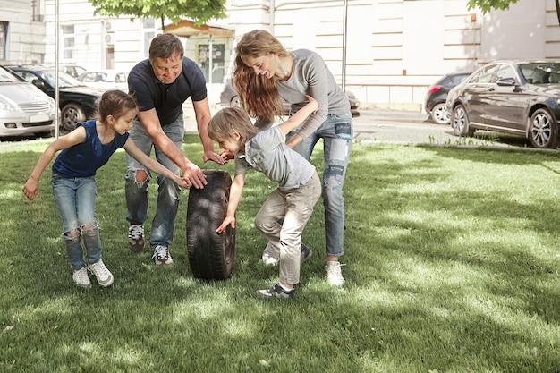 Pais com seus filhos brincando no pátio da cidade.