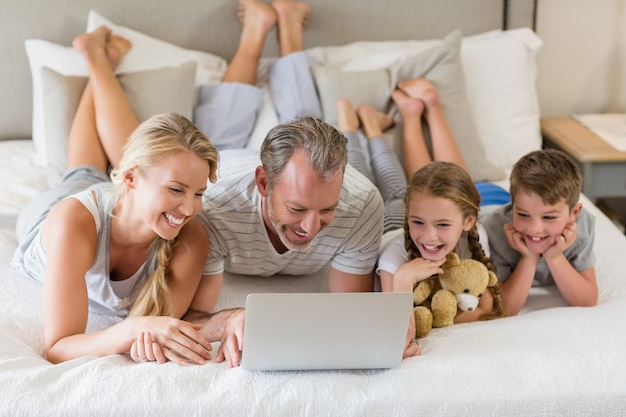 Pais com seus filhos, deitada na cama e usando o laptop