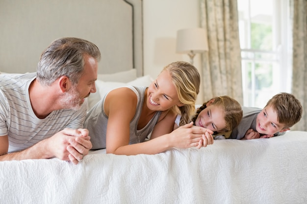 Pais com seus filhos, deitado na cama no quarto