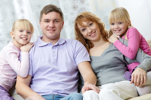 Pais com suas filhas que sentam-se no sofá