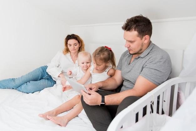 Pais com tablet na cama