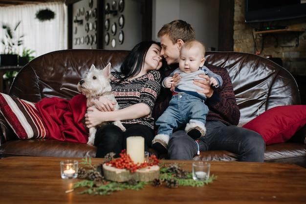 Pais com um bebê no natal e um cão sentado no sofá