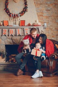 Pais com um cão e um bebê e uma guitarra que descansa no sofá