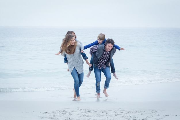 Pais correndo enquanto carregava filhos na beira-mar