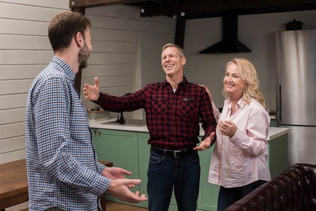 Pais dando as boas-vindas ao filho na cozinha