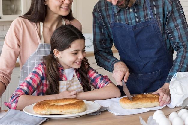 Pais de alto ângulo, ensinando a menina a cozinhar