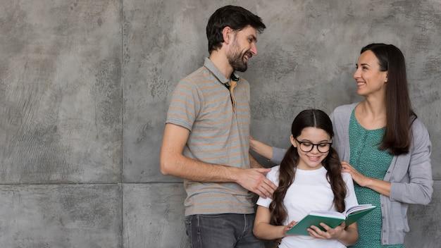 Pais de baixo ângulo, ajudando a menina a ler